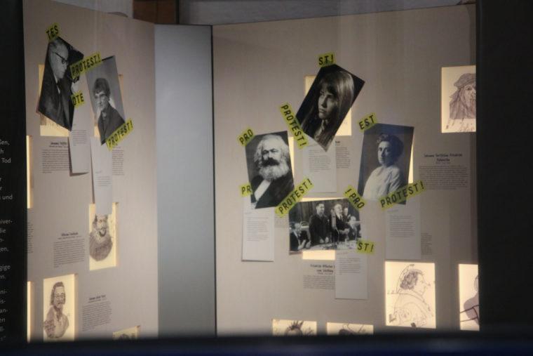 Ausstellungswand mit angehefteten Portraits
