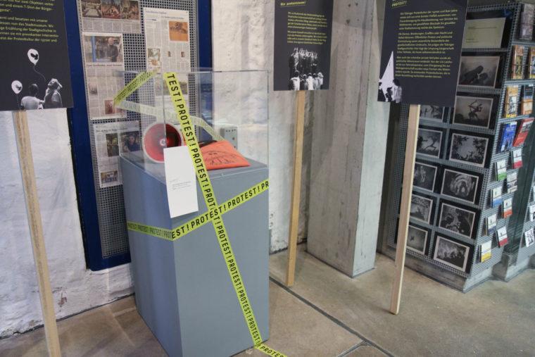 Mit Protest!-Absperrband beklebter Sockel der ursprünglichen Ausstellung