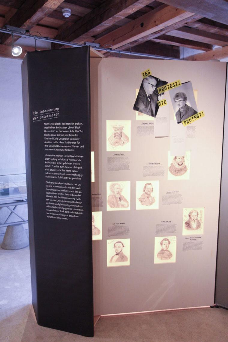 """Ausstellungswand """"Die Umbenennung der Universität"""" mit angehefteten Portraits"""